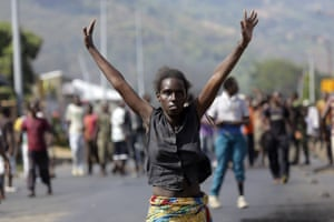 A demonstrator raises her hands in the air as she faces soldiers in Bujumbura, Burundi.