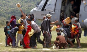 Villagers collect relief material from an Indian air force helicopter outside Pokhara on Friday.
