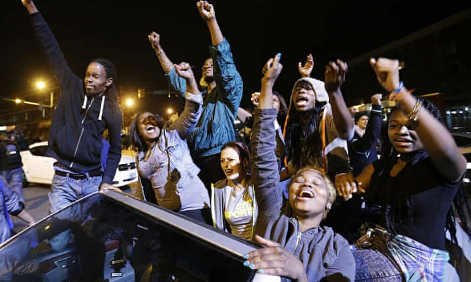 Demonstrators celebrate the announcement that six officers have been charged over the death of Fredd