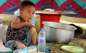 A young boy, Gigar Rama, eats lunch inside a temporary shelter in Kathmandu on Saturday.
