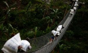 Villagers carry sacks of World Food Program aid over a bridge in Baluwa, Gorkha district.