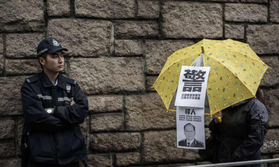 A Hong Kong policeman looks at a demonstrator holding an umbrella while taking part in a democracy march in 2014. Concerns over press freedom in the former British colony has led to the start up of a new independent newspaper.