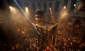 Christian pilgrims hold candles at Jerusalem's Church of the Holy Sepulchre, traditionally believed to be the burial site of Jesus Christ.
