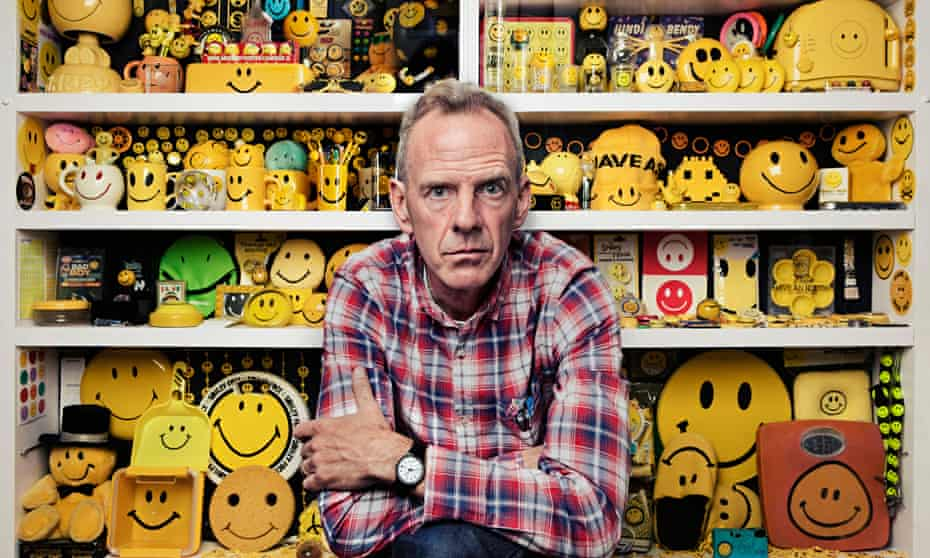 norman cook in front of shelves full of smiley faces