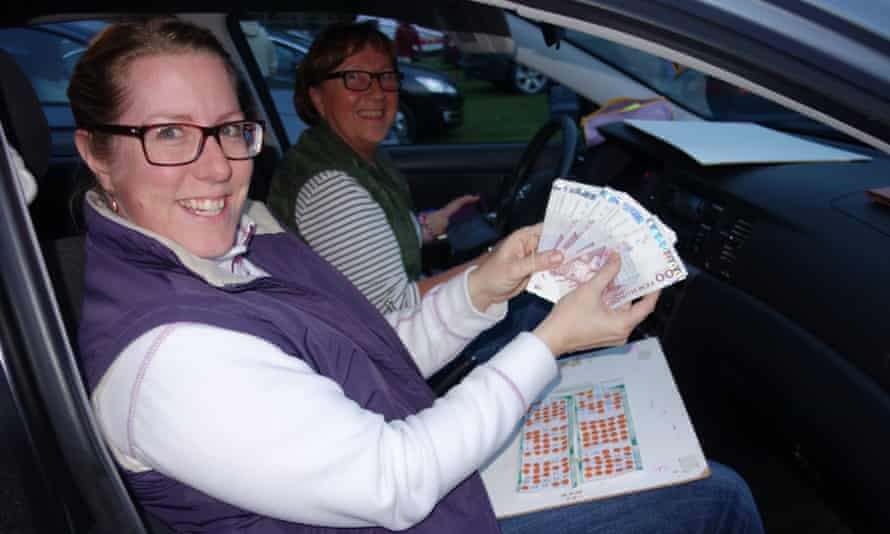 Two women show off their winnings after playing drive-in bingo in Sweden