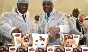 President of the Ivory Coast Alassane Ouattara (left) listens to Benjamain Bessie, the director general of the Cémoi Ivory Coast factory as he explains the production of chocolate.