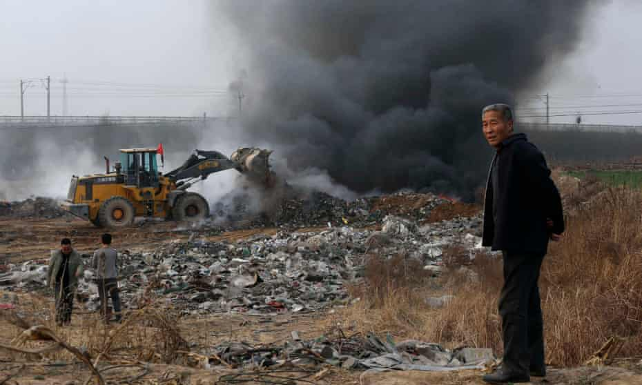 March 2014: a man looks on as a bulldozer piles up garbage to burn on the outskirts of Baoding.