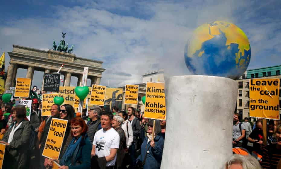 Environmental activists hold banners during a rally in front of the Brandenburg Gate near the venue for the Petersberg Climate Dialogue in Berlin