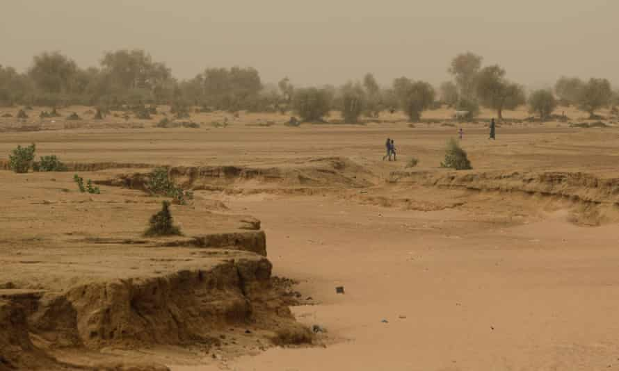 People walk past a dry riverbed in the Matam region of northeastern Senegal in the Sahel region of North Africa.