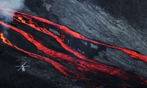 A helicopter flies over lava flowing from the Piton de la Fournaise volcano on the French island of La Reunion in the Indian Ocean