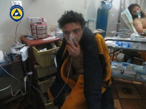 A victim of a chlorine attack holds an oxygen mask to his face at Sarmin hospital in a photograph taken by a Syrian civil defence group