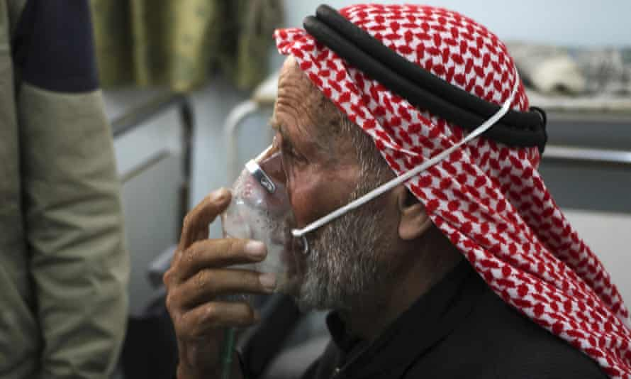 A man breathes through an oxygen mask after an alleged chlorine gas attack in Idlib