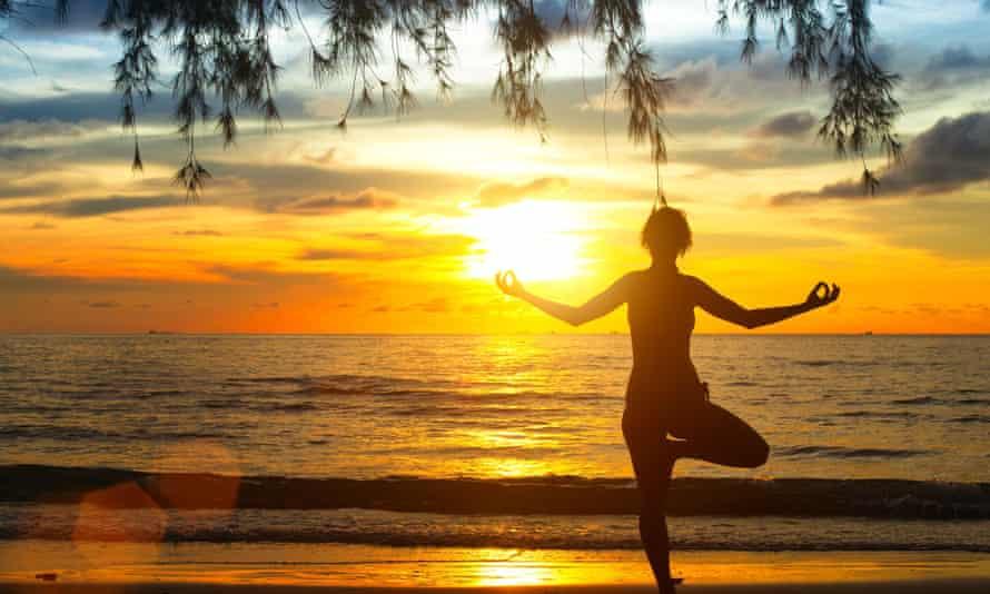 A woman meditates on a beach in Thailand.