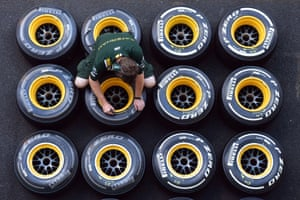 A Lotus F1 team mechanic marks wheels with Pirelli tyres