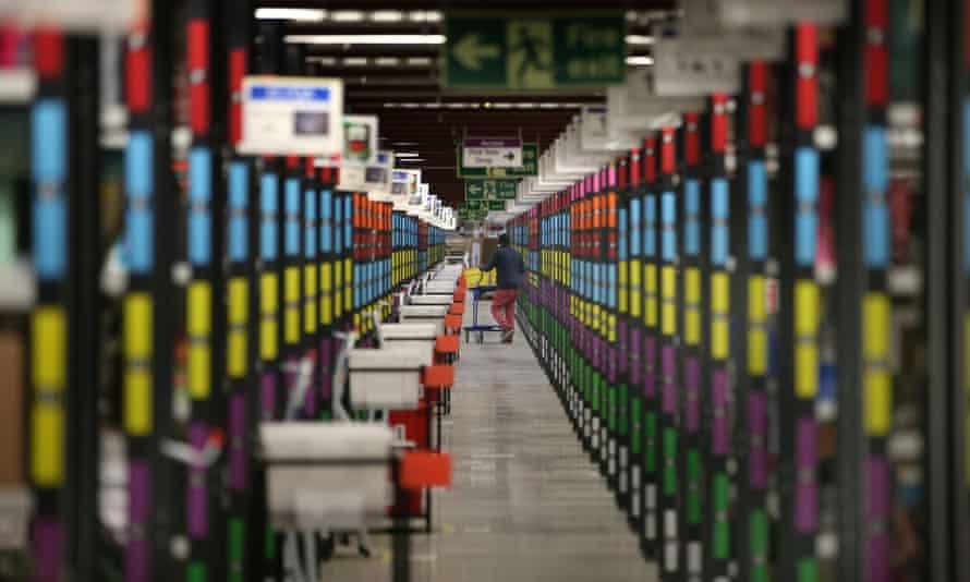 A worker retrieves goods from shelves at Amazon's warehouse n Hemel Hempstead.