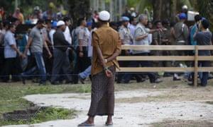 A Rohingya migrant watches as Indonesian officials visit a temporary shelter in Aceh Timur in Indonesia's Aceh province.