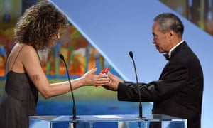 Taiwanese director Hou Hsiao-Hsien (R) receives the Best Director prize from Italian actress Valeria Golino during the closing ceremony of the 68th Cannes Film Festival in Cannes, southeastern France, on May 24, 2015.      AFP PHOTO / ANNE-CHRISTINE POUJOULATANNE-CHRISTINE POUJOULAT/AFP/Getty Images