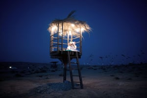 A couple dressed in costumes sit inside a hut during the festival, which takes place near the Israeli kibbutz of Sde Boker.