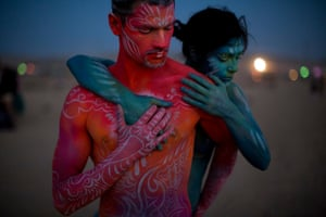 Israeli body artists embrace at dusk: the 2015 Midburn theme was transcendence, which the organisers described as 'reaching the boundaries of one's self and beyond the personal point of perception'. <em> </em>