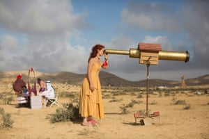 A festivalgoer pauses during the festival to look through a telescope to survey the sweeping Negev desert landscape