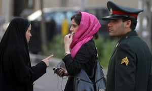 In a pre-summer ritual, an Iranian policewoman warns a young woman about her clothing and hair during a crackdown to enforce the Islamic dress code.