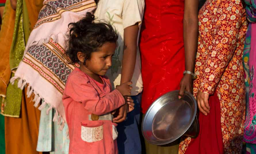A child lines up with her mother in a temporary shelter during food distribution at Tundikhel, in Kathmandu, Nepal.