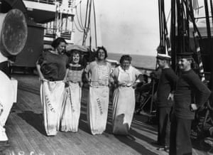 <strong> July 1923</strong> Four ladies compete in a sack race on the deck of the Cunard liner RMS Berengaria, watched by a couple of bemused sailors. The ship was originally the German vessel SS Imperator, and was given to the Cunard line as part of first world war reparations.