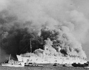 <strong>January 1972</strong> Smoke billows from the former RMS Queen Elizabeth after it caught fire in Hong Kong Harbour. The water poured on it by firefighters caused it to sink, ending a career which began in 1938.