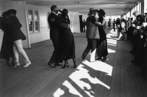 <strong> September 1922 </strong>Passengers dancing on the promenade around the deck of the RMS Aquitania upon her arrival at dock. It survived both world wars, returning to passenger service after each.