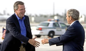 US President George W. Bush (R) reaches out to greet his brother, Governor Jeb Bush, as he arrives at Miami International Airport 30 July, 2006.