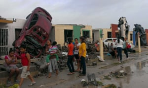 Cars flipped up on to houses in Ciudad Acuna after a tornado struck the city.