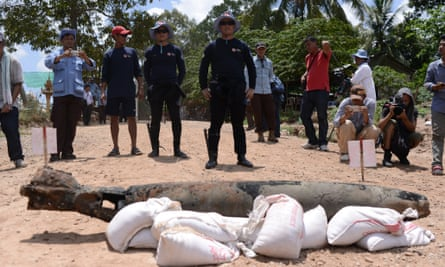 4387 - Standing in their scuba gear, UXO recovery divers Lorn Sarat (left) and Sok Chenda stand behind a US-manufactured Mark 82 aircraft bomb, which they salvaged from the Mekong River in Cambodia's Kandal province on May 21, 2015. Two years ago, neither man could swim.