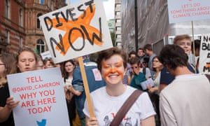 A young demonstrators smiles as he holds a placard, calling for institutions across the country to divest from fossil fuels