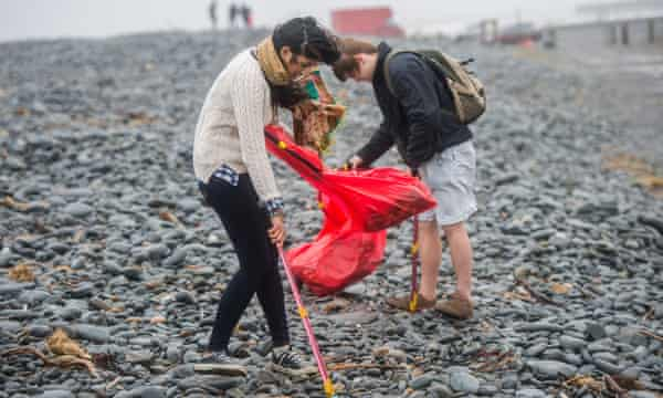 Students volunteering to clean litter off the beach at Aberystwyth in Wales  – you can also help at home.