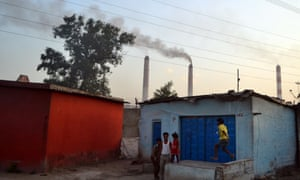 Children play out side their houses in  Vindhyanagar, Madhya Pradesh, while smoke belches out of the power station nearby.