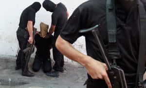 Hamas militants grab a Palestinian suspected of collaborating with Israel before being executed in Gaza City in August 2014.