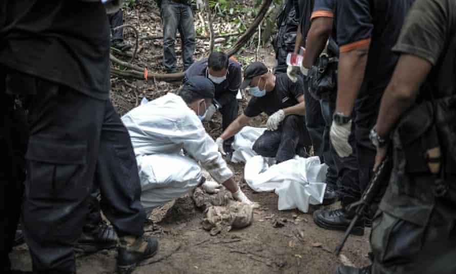 A Royal Malaysian Police forensic team handles exhumed human remains in a jungle at Bukit Wang Burma.