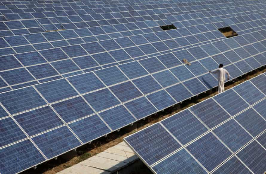 A worker cleans solar panels at the Azure Solar Plant in Gujarat, India.