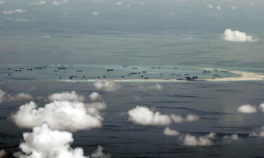 An aerial file photo taken though a glass window of a Philippines military plane shows land reclamation by China on a reef in the South China Sea.