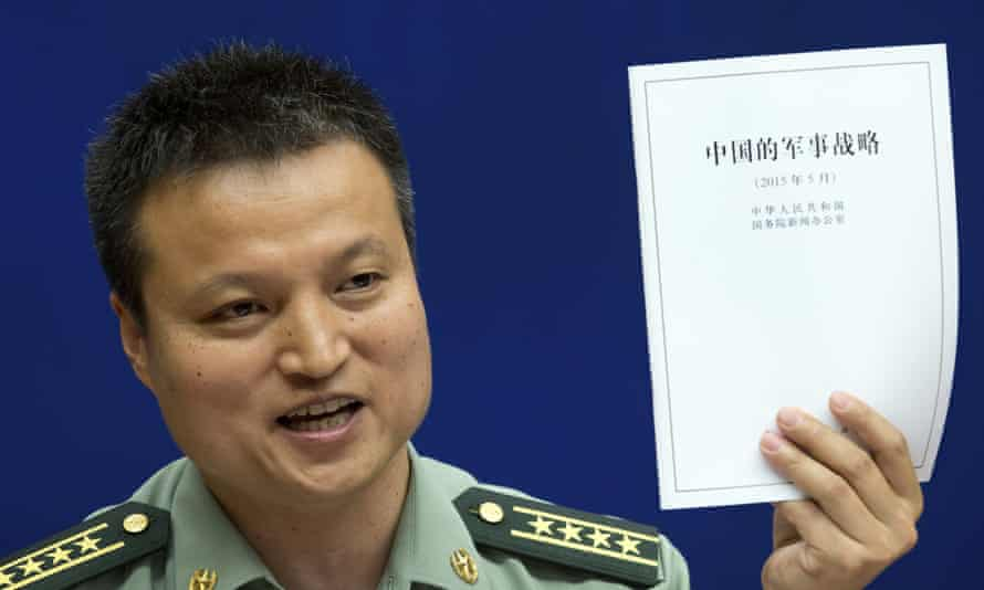 China's defense ministry spokesman Yang Yujun holds up a report on China's military strategy unveiled on Tuesday: China has compared its controversial island-building to ordinary infrastructure construction going on elsewhere in the country.