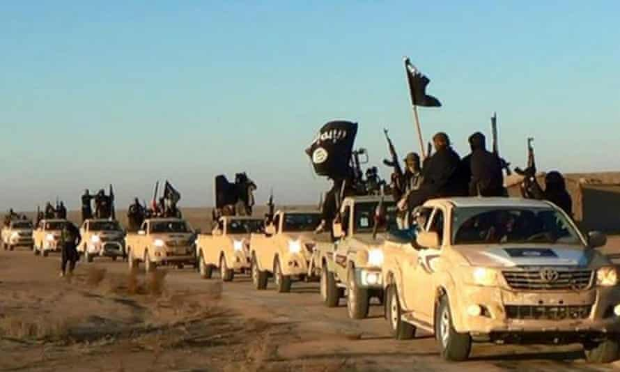 Islamic State fighters in a convoy on a road leading to Iraq from Syria.