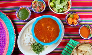 Mexican food on a red and pink striped table cloth.