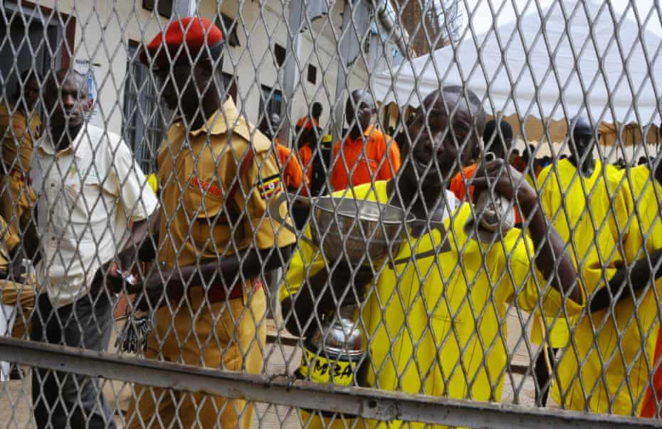 One of the Luzira prison inmates holds the Radio Simba football tournament trophy won by Manchester United.