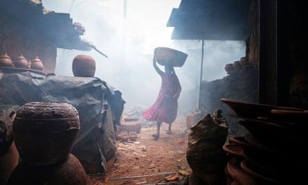 A woman potter carries earthen pots through traditional pottery kilns in the Mumbai slum of Dharavi, setting for Slumdog Millionaire.