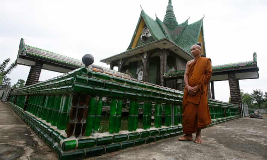 A Buddhist monk walks past the Wat Pa Maha Chedi Kaew temple, built with more than a million glass bottles, in Thailand's Sisaket province
