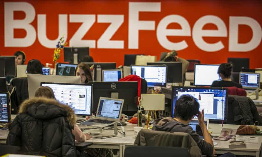 The BuzzFeed logo is displayed on the wall as employees work in the newsroom at the company's headquarters in New York.