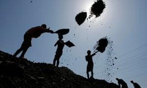 Labourers load coal on trucks