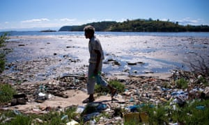 A man walks along the shoreline of the polluted waters of Guanabara Bay near Rio de Janeiro.