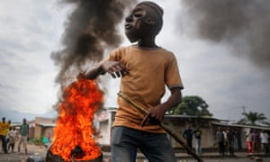A masked Burundian protester faces soldiers in front of a burning barricade during an anti-government demonstration against President Pierre Nkurunziza's bid for a third term in the capital Bujumbura