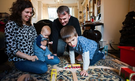 Liz Field and her husband at home with Cian, playing with a train set